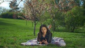 Jeune femme de sourire s'étendant sur la pelouse avec le PC de comprimé banque de vidéos