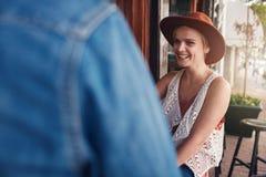 Jeune femme de sourire s'asseyant à un café avec son ami Image stock