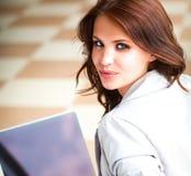 Jeune femme de sourire s'asseyant avec l'ordinateur portable photos stock