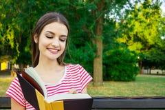 Jeune femme de sourire s'asseyant avec le journal intime faisant quelques notes en beau parc de ville photos stock