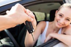 Jeune femme de sourire s'asseyant dans la voiture prenant la clé Image stock