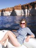 Jeune femme de sourire s'asseyant dans le bateau photos libres de droits