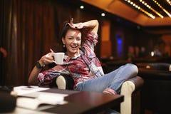 Jeune femme de sourire s'asseyant dans le café Image stock