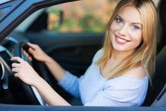Jeune femme de sourire s'asseyant dans le véhicule Images libres de droits