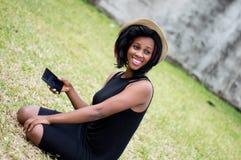 Jeune femme de sourire s'asseyant en parc avec un téléphone à disposition image stock