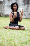 Jeune femme de sourire s'asseyant en parc et à l'aide d'un téléphone portable photo libre de droits