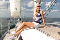 Jeune femme de sourire s'asseyant sur la plate-forme de yacht Photo libre de droits