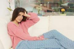 Jeune femme de sourire s'asseyant sur le sofa avec la couverture en hiver Photo libre de droits