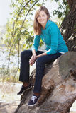 Jeune femme de sourire s'asseyant sur un arbre Photographie stock