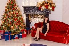 Jeune femme de sourire s'asseyant sur un divan rouge sur Noël jeune femme de brune dans la robe noire courte et des chaussures no photographie stock libre de droits