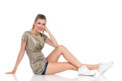 Jeune femme de sourire s'asseyant sur un plancher Images stock