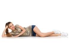 Jeune femme de sourire se couchant sur un plancher Image libre de droits