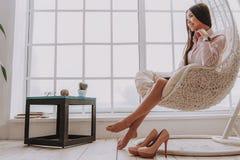 Jeune femme de sourire se reposant dans la chaise confortable photo libre de droits