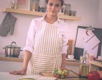 Jeune femme de sourire se tenant dans la cuisine photos stock
