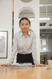 Jeune femme de sourire se tenant et se penchant sur la table dans le bureau, regardant l'appareil-photo, portrait Images stock