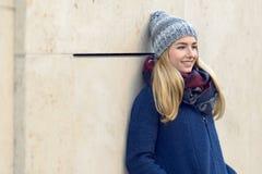 Jeune femme de sourire se tenant rêvassante Photo stock