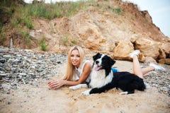 Jeune femme de sourire se trouvant avec son chien sur la plage Image libre de droits