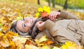Jeune femme de sourire se trouvant sur des lames en automne Photographie stock libre de droits