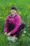 Jeune femme de sourire à sélectionner les fraisiers communs Photographie stock