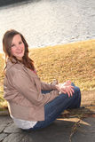 Jeune femme de sourire sur des escaliers par l'eau Image libre de droits