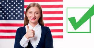 Jeune femme de sourire sur le fond de drapeau des Etats-Unis Photos libres de droits