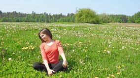 Jeune femme de sourire sur le gisement de pissenlit Image stock