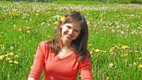 Jeune femme de sourire sur le gisement de pissenlit Photographie stock