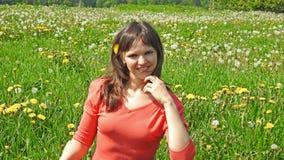 Jeune femme de sourire sur le gisement de pissenlit Photo stock