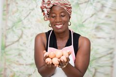 Jeune femme de sourire tenant des oeufs photo stock