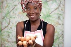 Jeune femme de sourire tenant des oeufs dans la main photos libres de droits