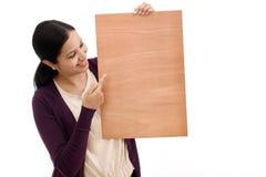 Jeune femme de sourire tenant la feuille en bois vide photographie stock