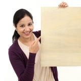 Jeune femme de sourire tenant la feuille en bois vide photo libre de droits