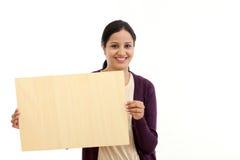 Jeune femme de sourire tenant la feuille en bois vide photos stock