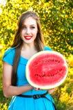 Jeune femme de sourire tenant la moitié de la pastèque juteuse Image libre de droits