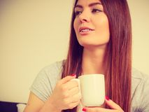 Jeune femme de sourire tenant la tasse de thé photographie stock