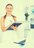 Jeune femme de sourire tenant le dossier avec des documents Image stock