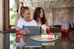 Jeune femme de sourire tenant le pavé tactile avec l'espace de copie pour votre marque tout en se reposant avec ses amis en café, Photo stock