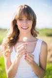 Jeune femme de sourire tenant le pissenlit Photographie stock