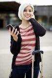 Jeune femme de sourire tenant le téléphone intelligent en dehors de la gare Images stock