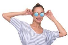 Jeune femme de sourire utilisant les lunettes de soleil modernes image stock