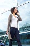 Jeune femme de sourire voyageant avec le sac et le téléphone portable Photos libres de droits