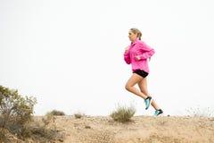 Jeune femme de sport coulant de la route sale de traînée de route avec le fond sec de paysage de désert s'exerçant dur Image libre de droits