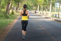 Jeune femme de sport de forme physique courant sur la route pendant le matin, fusée de lumière de Sun photos stock
