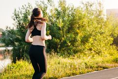 Jeune femme de sports occupée dans le matin d'été fonctionnant en parc sur un tapis roulant d'asphalte Mode de vie sain de concep image stock