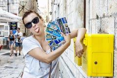 Jeune femme de touristes avec le postcarsd près de la boîte jaune de courrier dans Trogi images stock