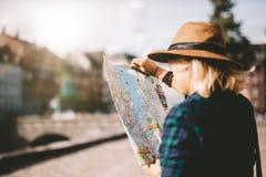 Jeune femme de touristes recherchant la bonne direction sur la carte Image stock