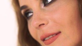 Jeune femme de visage semblant la fin latérale  Belle femme de portrait d'isolement sur le fond blanc de studio Fin vers le haut banque de vidéos