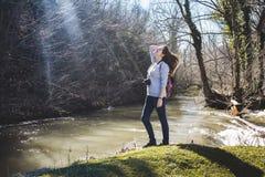 Jeune femme de voyageur avec le sac à dos ayant l'amusement par la rivière, enjo image stock