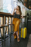 Jeune femme de voyageur avec une valise sur sa pause-café Photos libres de droits