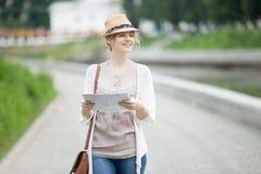 Jeune femme de voyageur dans le chapeau de paille marchant avec la carte en voyage photo libre de droits